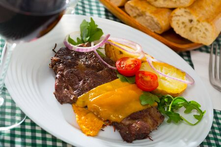 Spicy well done veal steak roasted with cheese slices served with baked potato, fresh tomatoes, onion and greens Фото со стока