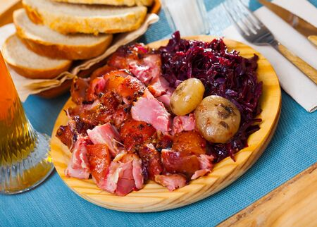 Image of baked pork knuckle with red cabbage and baked onion served  at plate