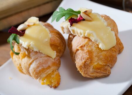 Image of mini croissant with Camembert, roasted pine nuts and arugula Imagens