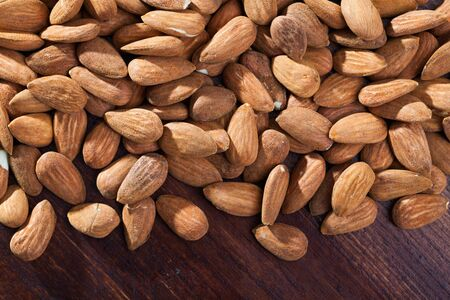 View of roasted almonds freely laid on wooden table