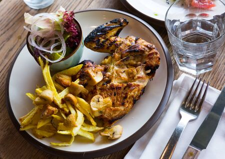 Delicious grilled chicken with chimichurri sauce, baked vegetables, fresh lettuce and onion
