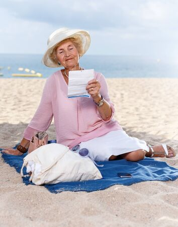 Happy retired woman sitting relaxed on sand at beach