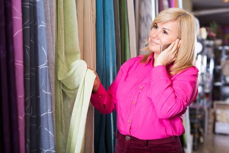 adult woman choosing curtains and using phone in the curtains shop
