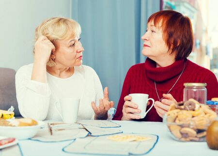 Two serious elderly women discussing something over cup of tea at home