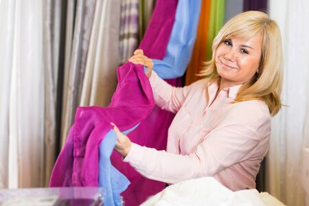 Mature woman customer choosing color curtains  in curtains shop