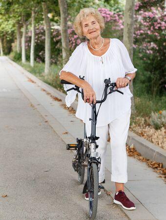 Senior caucasian woman having break in cycling, resting near bike