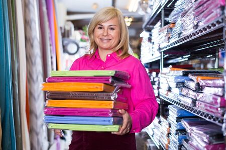 Positive mature female demonstrating colored bed sheet stack in store