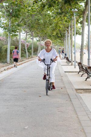 Portrait of happy mature female bicyclist riding on embankment Stock Photo - 124924570