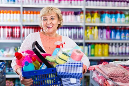 Cheerful positive woman consumer with household chemical products in basket for cleaning Фото со стока