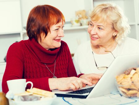 Portrait of two happy senior women using laptop sitting at table at home