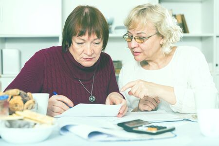 Two mature female friends looking worriedly at papers at home