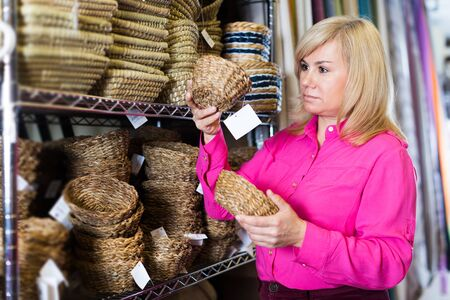 Adult female standing with wicker basket in store for decor 版權商用圖片