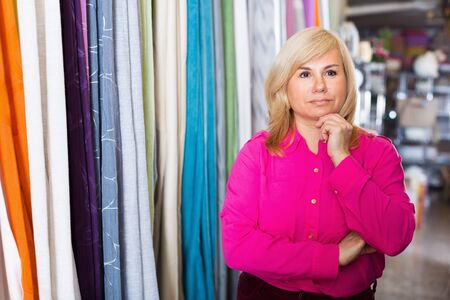 Portrait of  mature female standing among shelf in the curtains shop Imagens