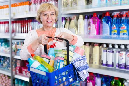Woman consumer with household chemical products in basket for cleaning