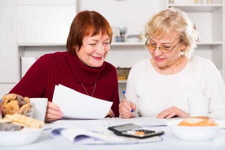 Portrait of cheerful mature females with documents communal payments