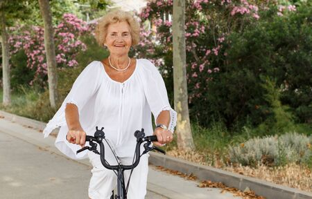 Smiling senior lady riding modern bike in summer nature