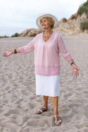 Happy senior woman standing at seaside and admiring nature 版權商用圖片