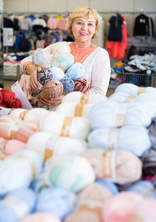 Cheerful positive smiling mature woman buyer choosing colored yarn for knitting on sale