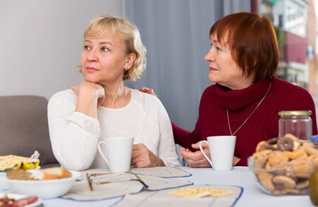 Mature lady trying to calm her female friend and apologize after quarrel Stock Photo