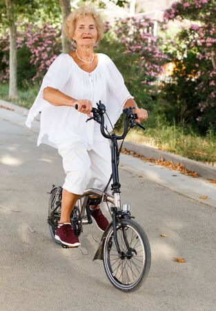 Casual mature woman on bike cycling in summer park
