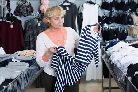 Adult woman purchaser choosing striped dress in the shopping center