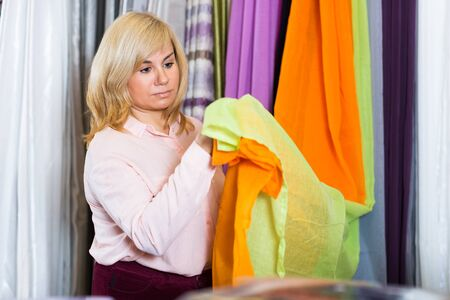 adult customer choosing color curtains  in curtains store