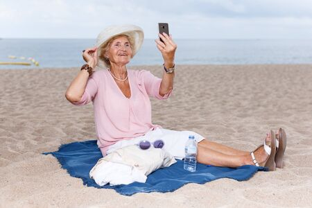 Senior woman taking selfie with phone while resting at beach 版權商用圖片