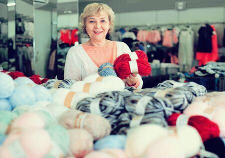 Happy cheerful glad  smiling mature woman buyer choosing colored yarn for knitting on sale 版權商用圖片