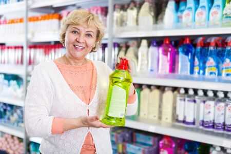 Smiling female customer holding chemical goods for cleaning home in the  store 版權商用圖片