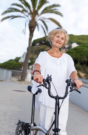 Active elderly woman walking with bike on park path