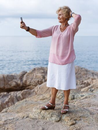 Smiling senior lady relaxing on beach walk and making selfie