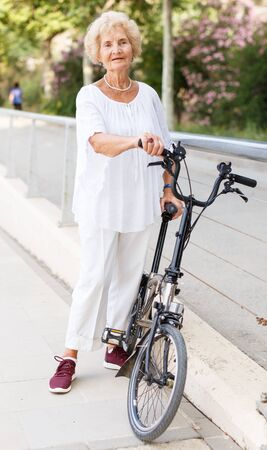 Positive mature woman standing and relaxing after bicycle walk