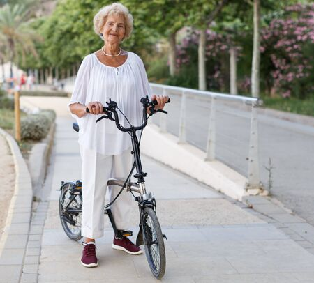Portrait of casual senior woman going to bike at summer day