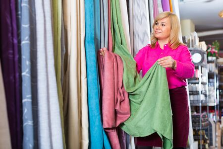 Positive mature female choosing curtains in the curtains shop Imagens