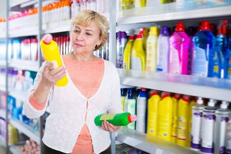 Adult woman buyer choosing household chemical goods in the store