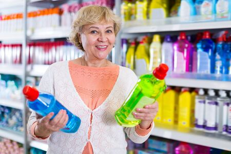 Happy woman buyer choosing household chemical goods in the store