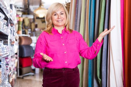 Positive mature female  seller offering curtain  in the curtains store