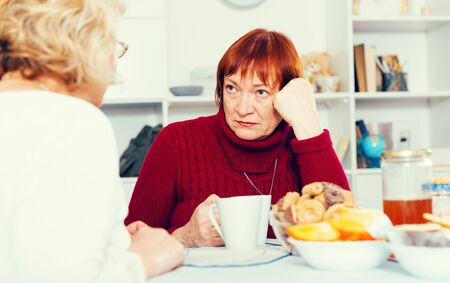 Stressed senior woman having conversation with female over cup of coffee at home Stock Photo