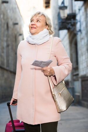 portrait of mature female tourist holding map and baggage 版權商用圖片