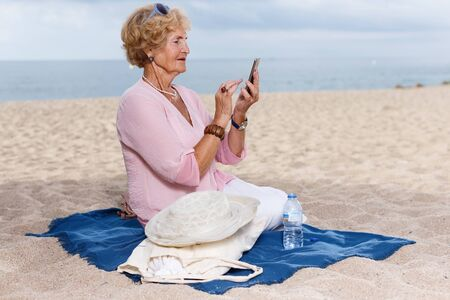 Positive senior woman using mobile phone during seaside walk