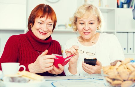 Couple of positive mature females sitting with telephone indoors