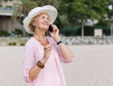 Portrait of senior lady making phone call while resting at beach
