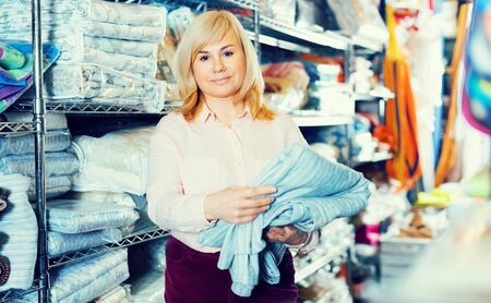Portrait of mature woman holding cotton bed cover in the store