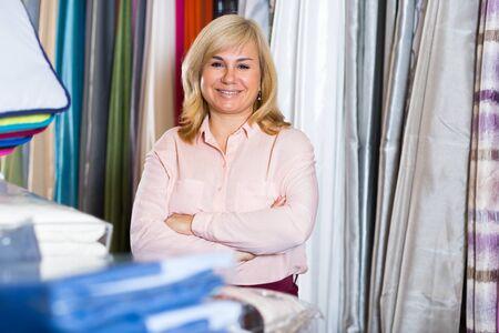 Positive mature woman standing among shelf in the textile shop 版權商用圖片