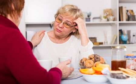 Senior woman calming her chagrined female friend over cup of tea at home