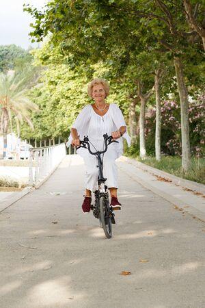 Smiling senior lady riding modern bike in summer nature