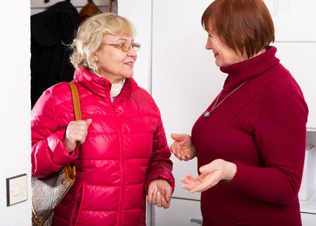 Happy senior woman meeting her female friend and welcoming to apartment