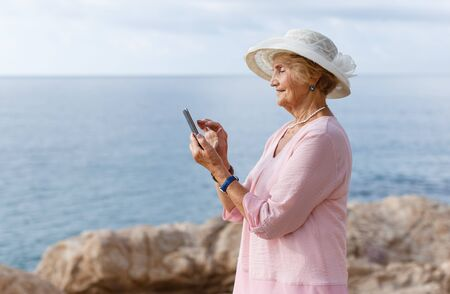 Portrait of a smiling senior woman holding smartphone resting at seashore