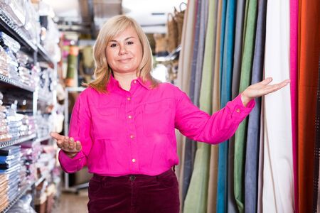Smiling mature woman seller showing curtain in the curtains shop
