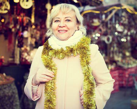 Positive female in tinsel on Christmas fair decoration on holiday 版權商用圖片